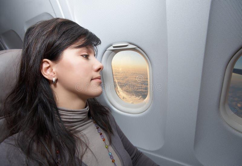 La mujer está en asiento de pasajero en el aeroplano fotografía de archivo libre de regalías