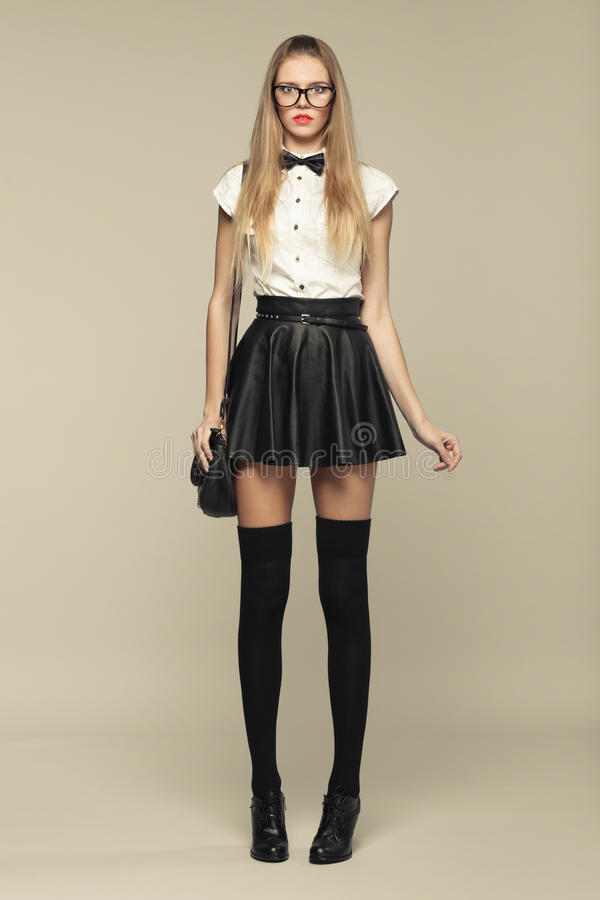 La mujer está en estilo de la moda en mini falda negra imagen de archivo