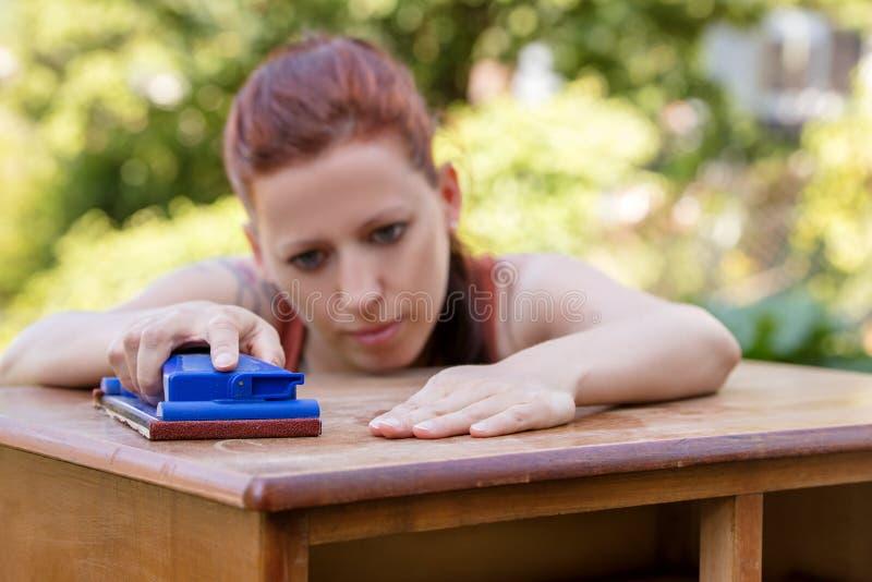 La mujer está enarenando a mano imagen de archivo libre de regalías