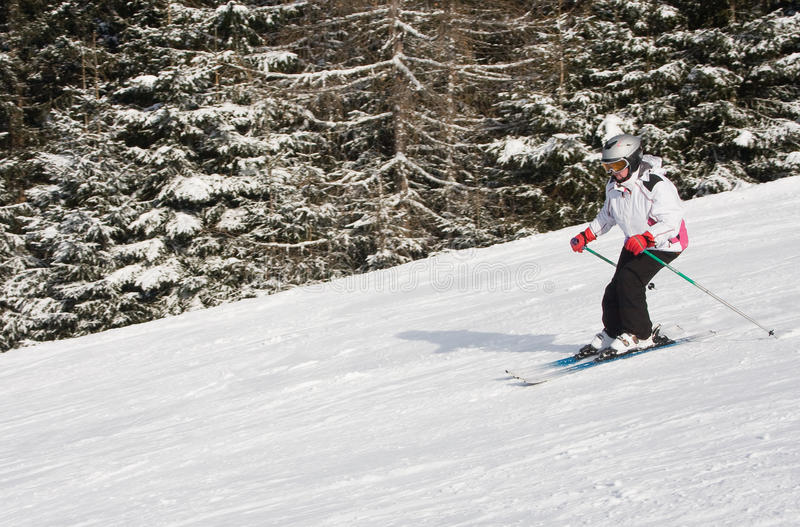 La mujer está esquiando en una estación de esquí imagenes de archivo