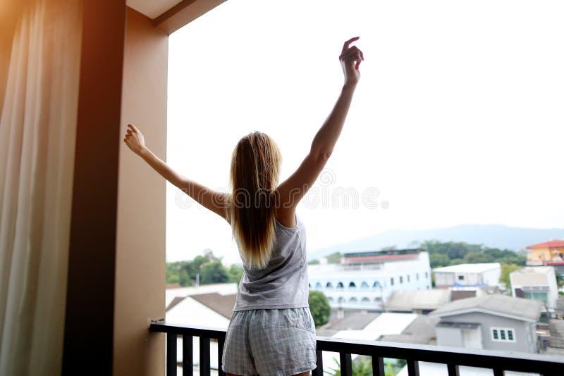 La mujer está estirando después de que sueño en balcón que disfruta de viaje imagen de archivo libre de regalías