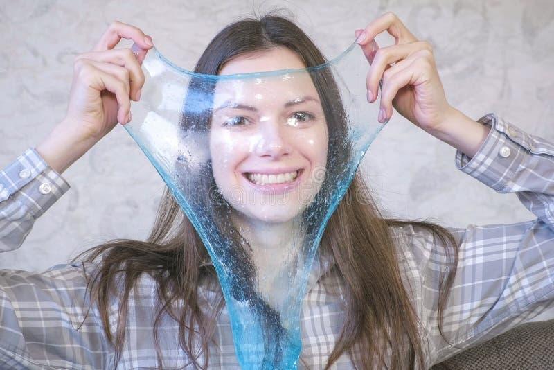 La mujer está estirando un limo azul que se sienta en el coche y jugar Mirada a través del limo imagen de archivo libre de regalías