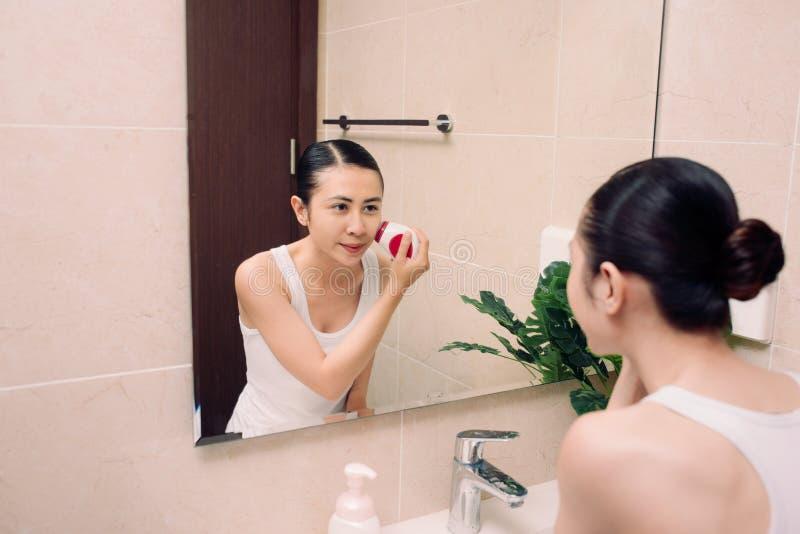 La mujer está limpiando su cara con un cepillo para la limpieza profunda imagen de archivo libre de regalías