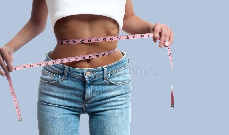 La mujer está midiendo la cintura después de pérdida de peso en fondo en colores pastel fotografía de archivo