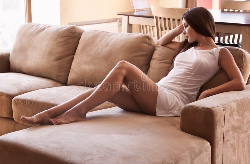 La mujer está mintiendo en un sofá fotos de archivo