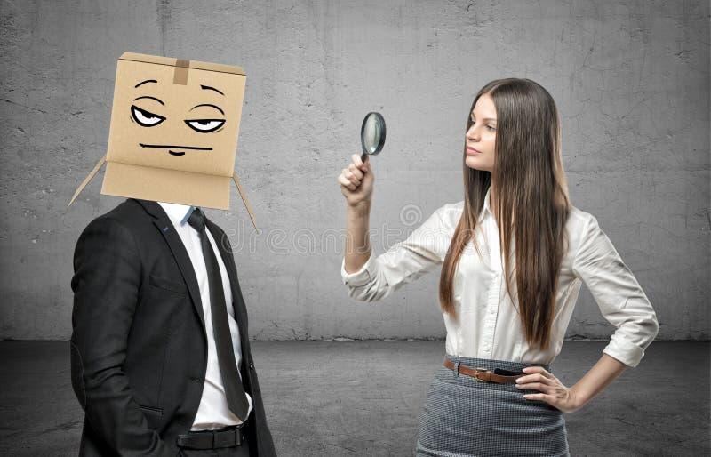 La mujer está mirando a través de una lupa un hombre de negocios con una caja en su cabeza con un pokerface foto de archivo libre de regalías