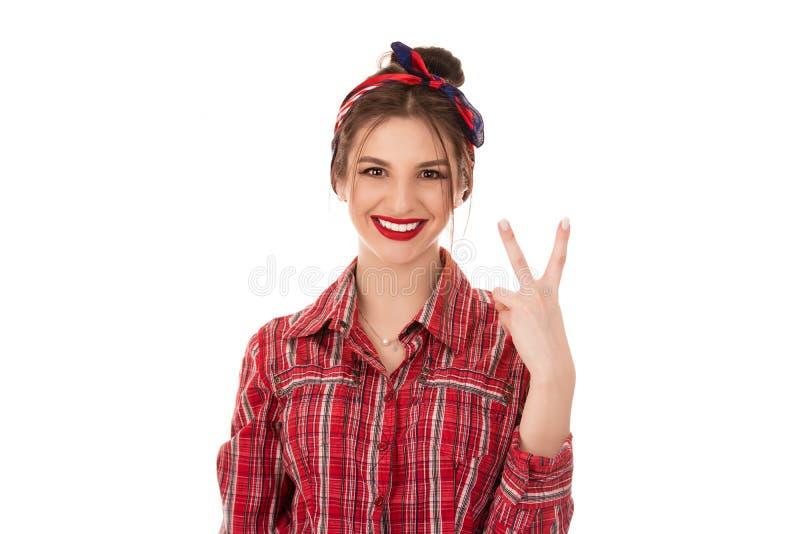 La mujer está mostrando paz, la muestra de la victoria y la sonrisa foto de archivo