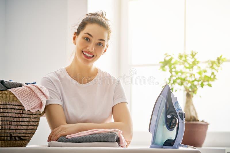 La mujer está planchando en casa imagenes de archivo