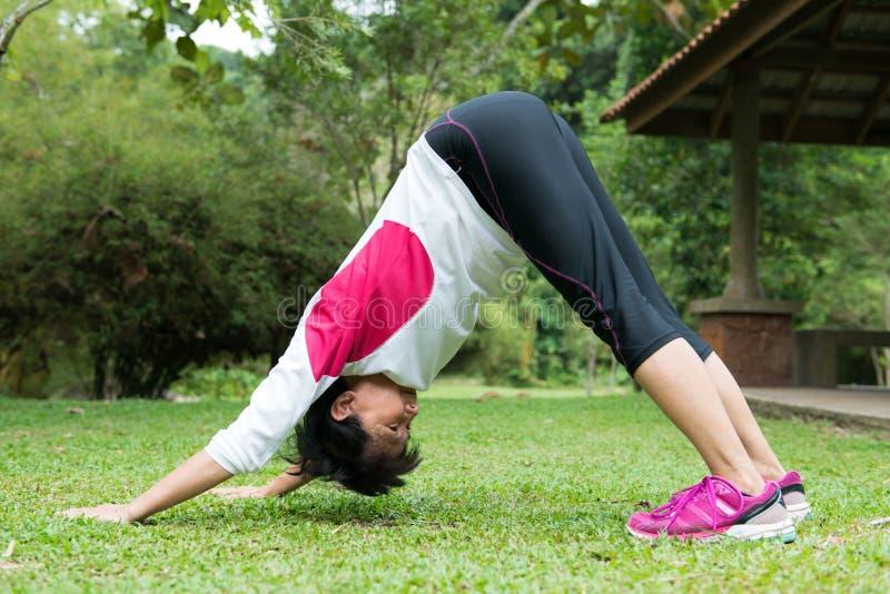 La mujer está practicando yoga en parque fotos de archivo libres de regalías