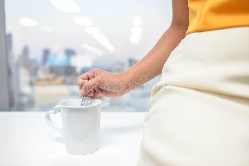 La mujer está revolviendo el café imagenes de archivo