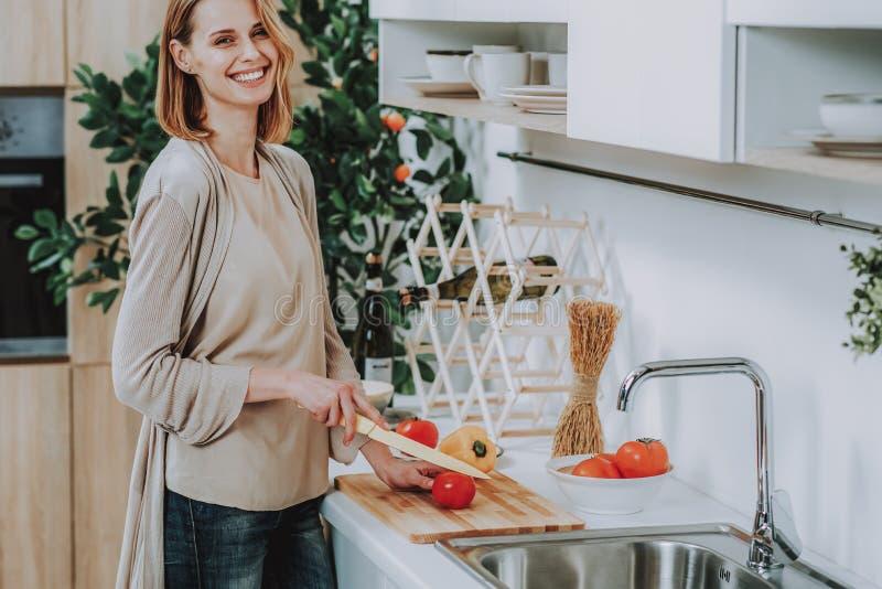 La mujer está riendo mientras que hace el plato en casa fotografía de archivo