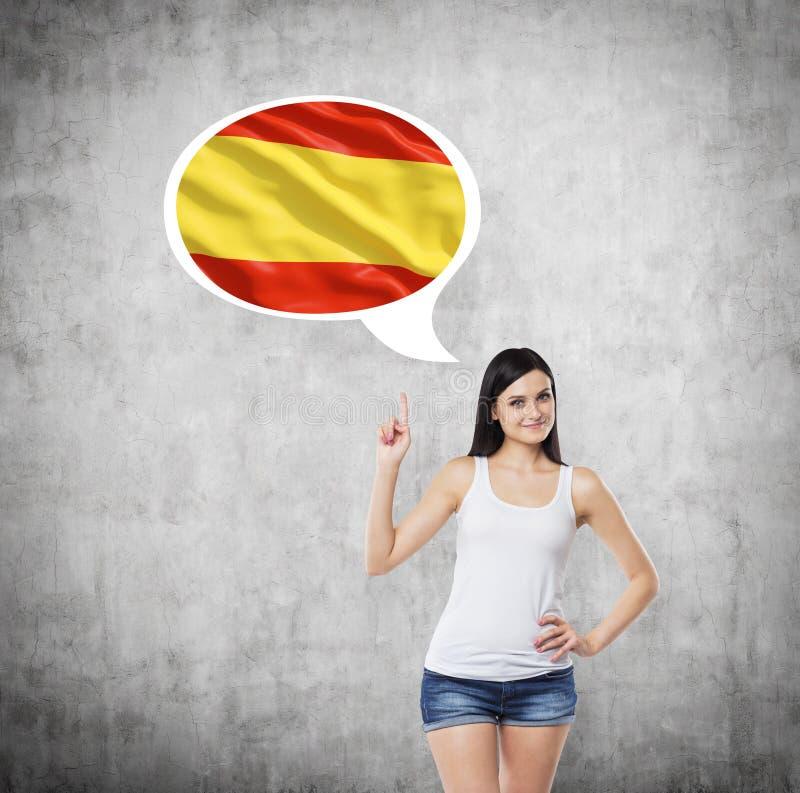 La mujer está señalando la burbuja del pensamiento con la bandera española Fondo concreto fotos de archivo libres de regalías