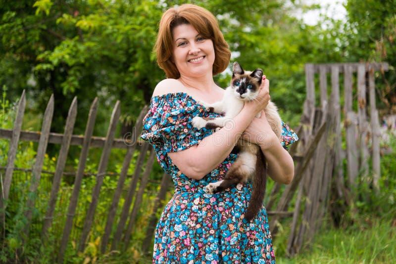 La mujer está sosteniendo el gato contra la perspectiva de la cerca rural imagen de archivo libre de regalías