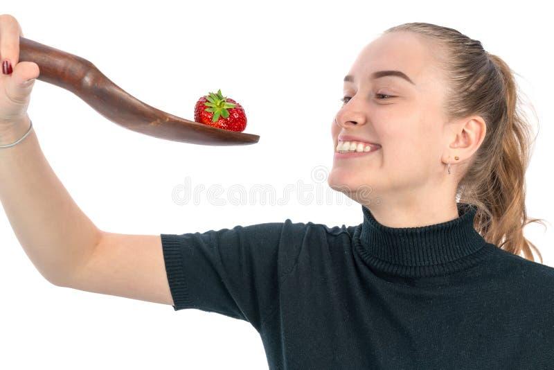 La mujer está sosteniendo una cuchara enorme con una fresa en ella para comerla imágenes de archivo libres de regalías