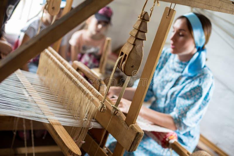 La mujer está tejiendo el traje o el vestido colorido del algodón usando telar de madera en el pueblo local en Rusia imágenes de archivo libres de regalías