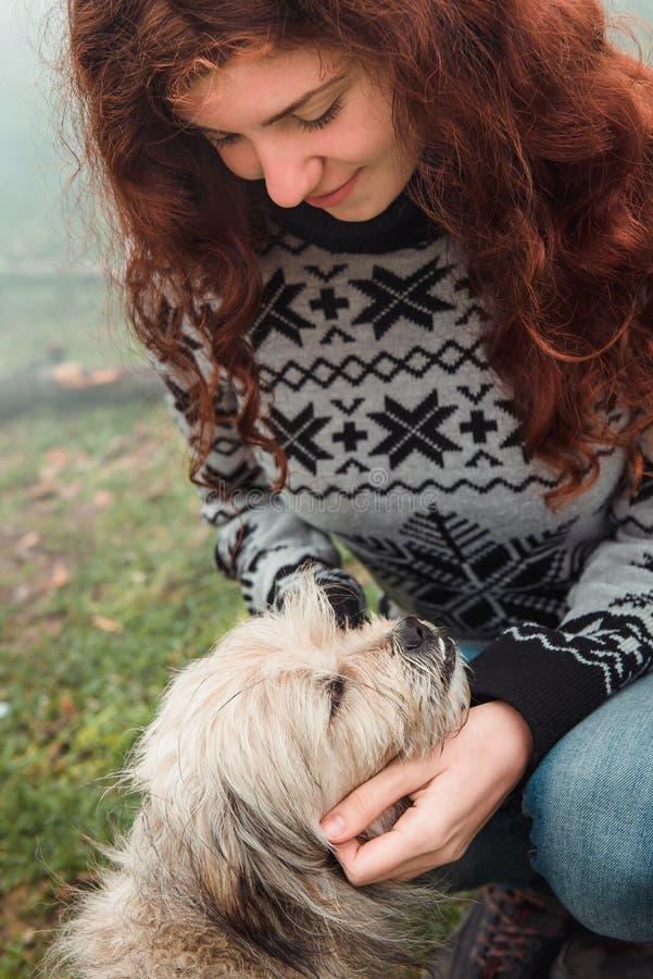 La mujer está tomando cuidado del perro sin hogar fotografía de archivo libre de regalías
