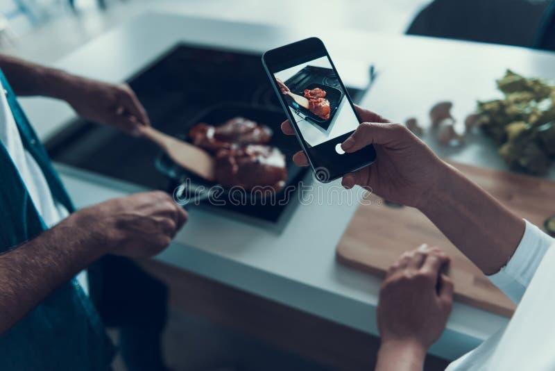 La mujer está tomando imágenes en el teléfono mientras que el hombre está cocinando la carne imagen de archivo