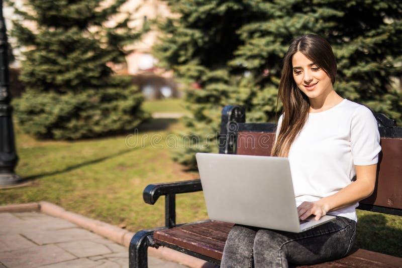 La mujer está trabajando en el ordenador portátil fuera de la oficina en un banco imagen de archivo libre de regalías