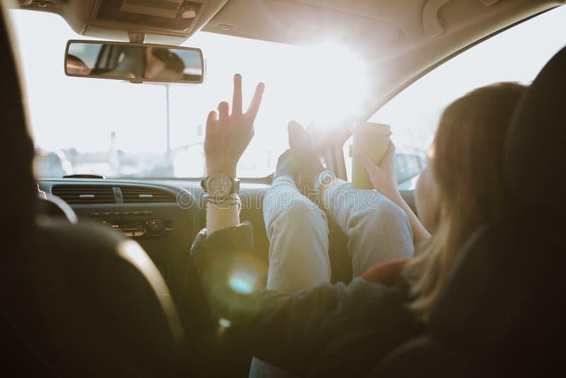 La mujer está utilizando gesto de la muestra de V dentro del coche fotografía de archivo