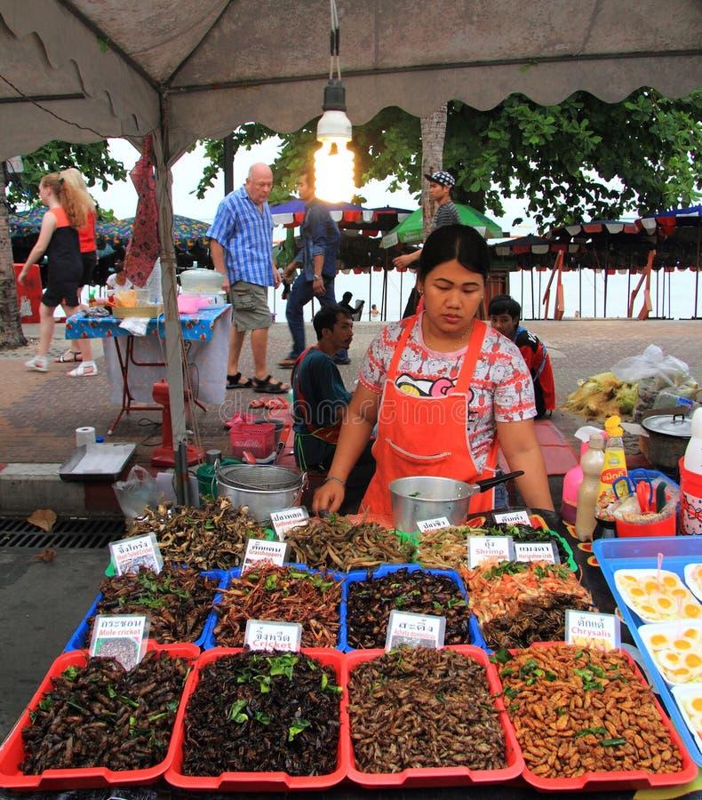 La mujer está vendiendo insectos fritos en el mercado fotos de archivo