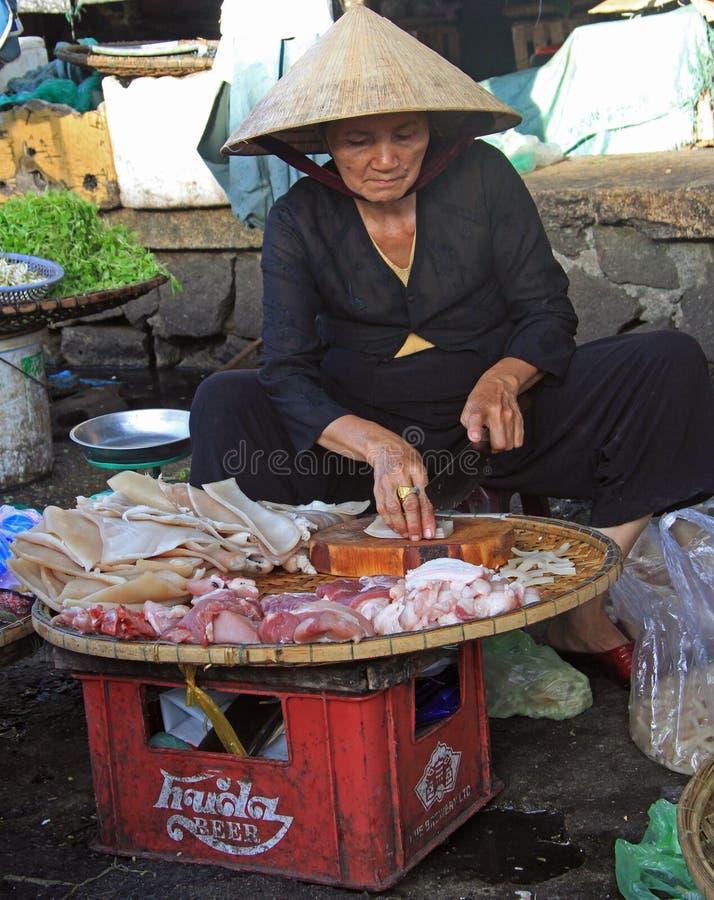 La mujer está vendiendo la carne en el mercado callejero en tonalidad, Vietnam fotos de archivo