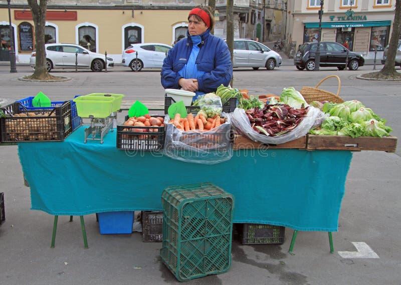 La mujer está vendiendo verduras en el mercado callejero en Ljubljana, Eslovenia foto de archivo libre de regalías