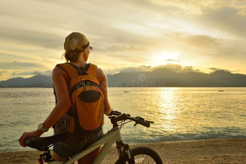La mujer está viajando con una mochila en su bicicleta imagenes de archivo