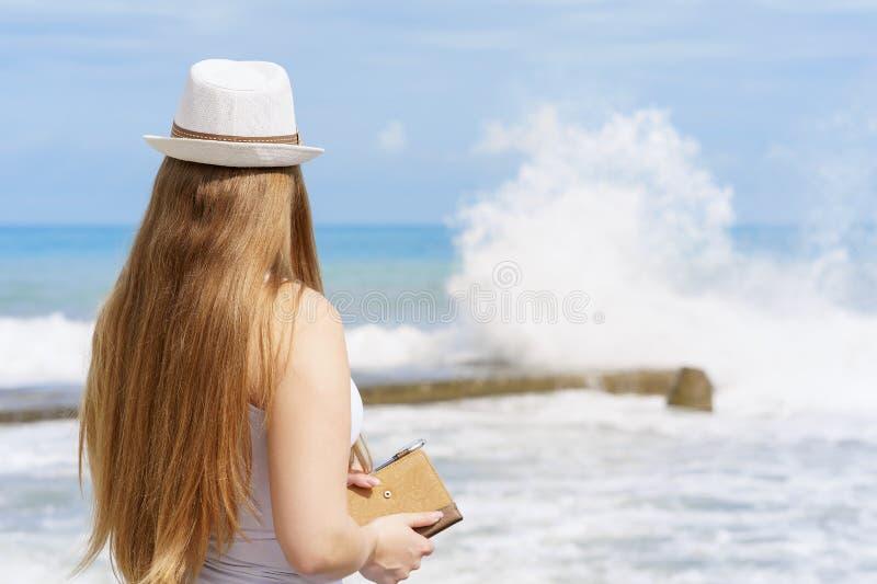 La mujer europea atractiva joven con la libreta y la pluma está permaneciendo cerca de la playa del mar tropical azul en el fondo imágenes de archivo libres de regalías
