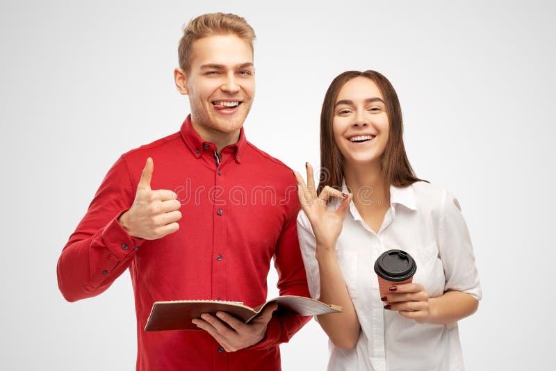 La mujer europea confiada satisfecha y el hombre hermoso con la sonrisa amplia, peinado elegante, muestra gesto de la autorizació imagen de archivo