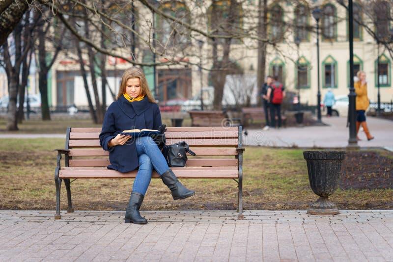 La mujer europea joven con la capa azul está leyendo un poco de libro mientras que ella que se sienta en banco en parque en el ti imagenes de archivo