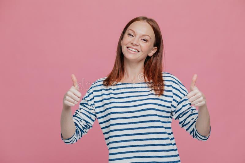 La mujer europea joven positiva con el pelo rojizo mantiene dos pulgares aumentados, inclina la cabeza, vestida en ropa rayada, d fotografía de archivo