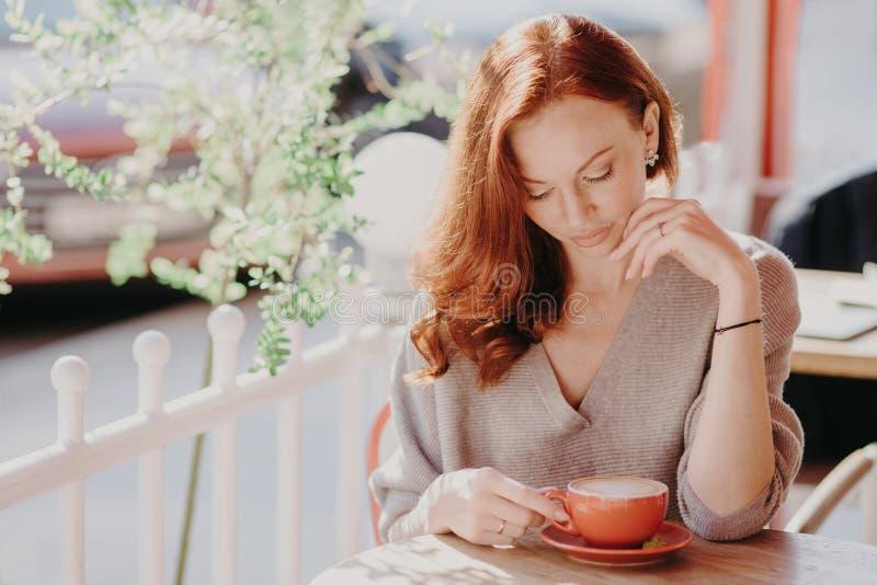 La mujer europea pelirroja encantadora bebe capuchino o el café en el café de la terraza, tiene expresión facial tranquila, lleva imagen de archivo libre de regalías