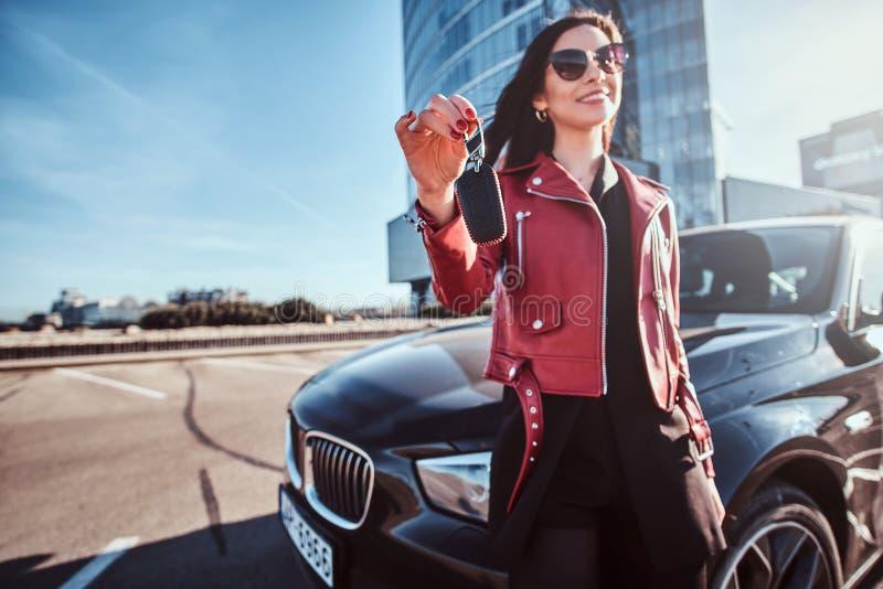 La mujer feliz acaba de conseguir llaves de su nuevo coche como regalo en día soleado brillante imagen de archivo
