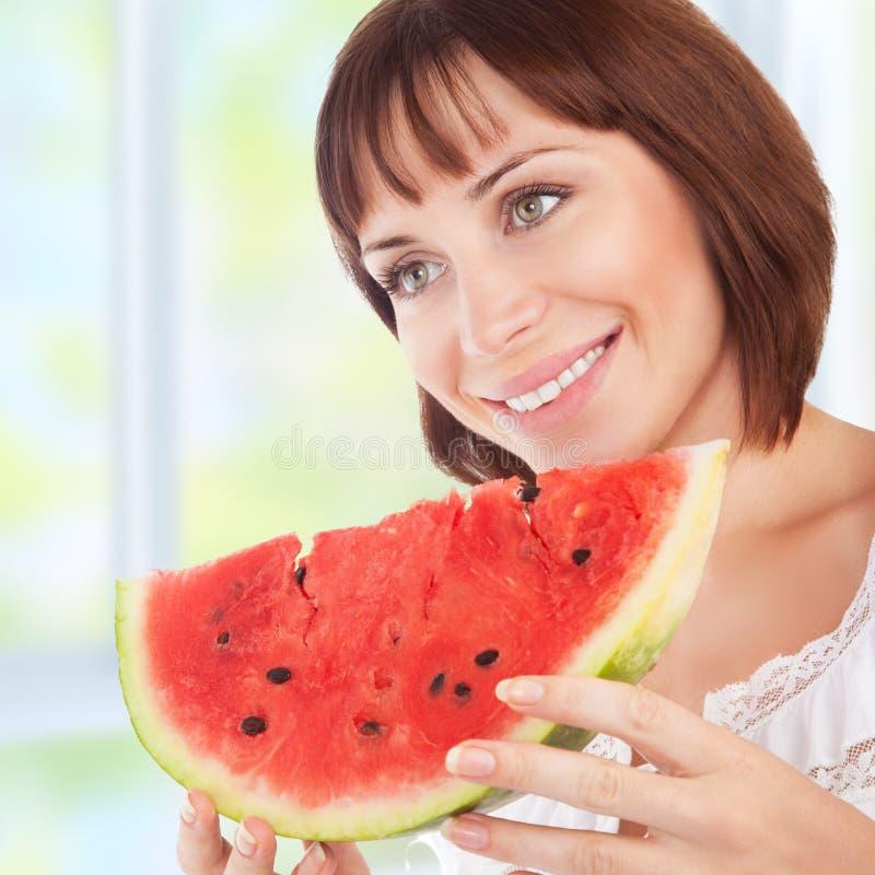 La mujer feliz come la sandía fotos de archivo