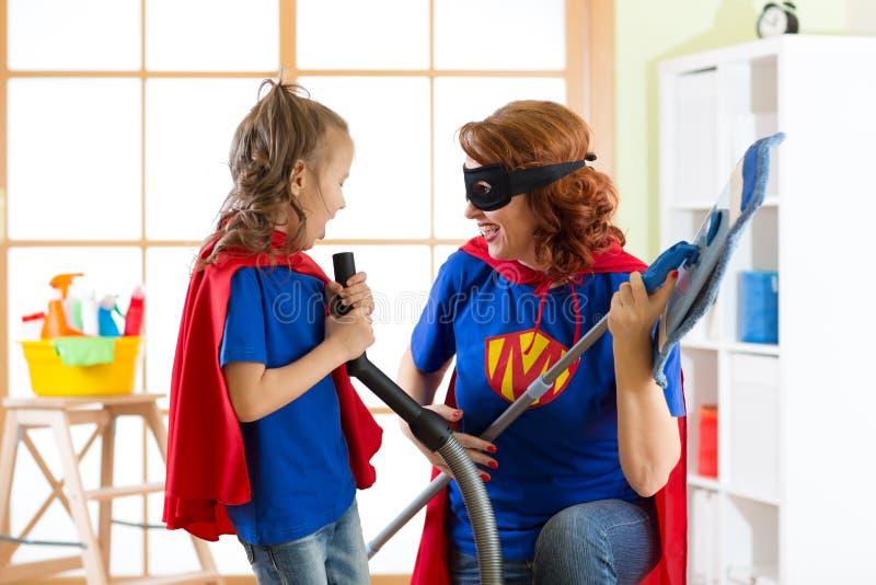 La mujer feliz con el sitio de limpieza del niño y se divierte Muchacha de la madre y del niño que juega junto Familia en trajes  imagen de archivo libre de regalías