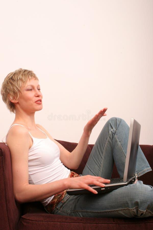 La mujer feliz con la computadora portátil está hablando con alguien fotos de archivo