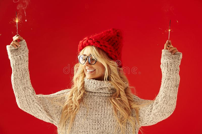 La mujer feliz con las luces de Bengala en sus manos que sonríe en fondo rojo aislado, lleva un suéter y un sombrero del invierno fotos de archivo
