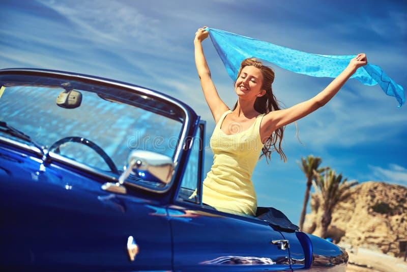 La mujer feliz con las manos aumentó sentarse en coche retro fotografía de archivo