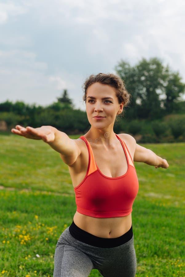 La mujer feliz de emisión del gimnasta que equilibra en yoga presenta foto de archivo