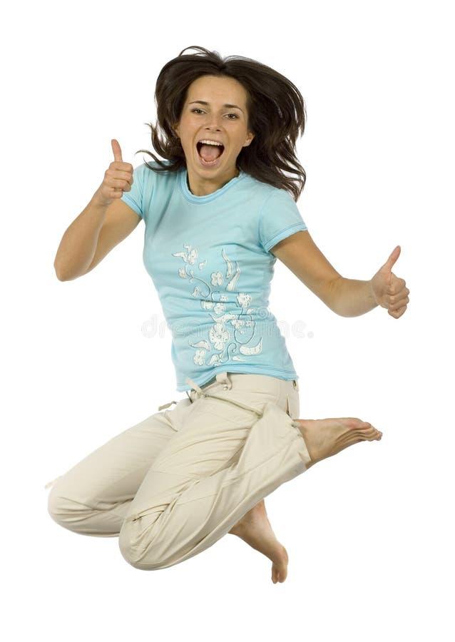 La mujer feliz de salto muestra OK fotografía de archivo