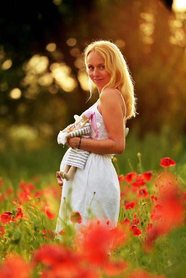 La mujer feliz embarazada en una amapola floreciente coloca al aire libre fotografía de archivo