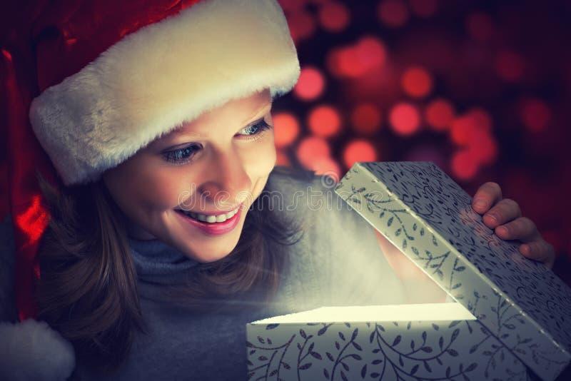 La mujer feliz en un casquillo de la Navidad abre la caja mágica fotos de archivo