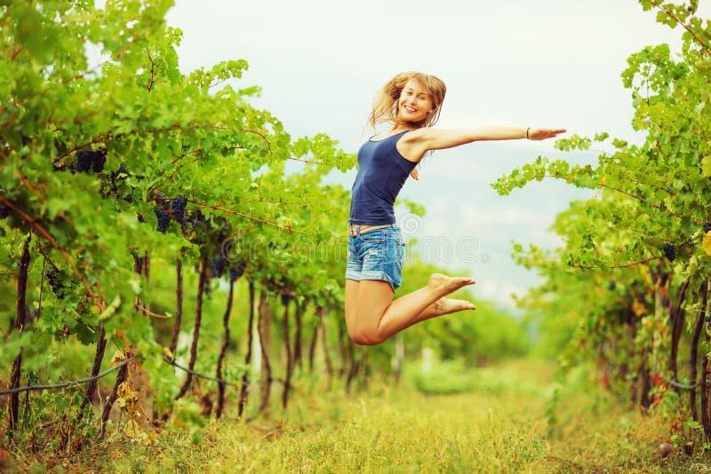 La mujer feliz en un viñedo está saltando y se está divirtiendo durante el h imagen de archivo