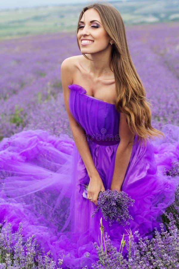 La mujer feliz en vestido púrpura de la moda en la lavanda coloca imagenes de archivo