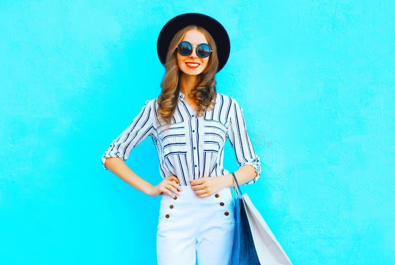 La mujer feliz es el llevar los panieres, sombrero negro, pantalones blancos imágenes de archivo libres de regalías
