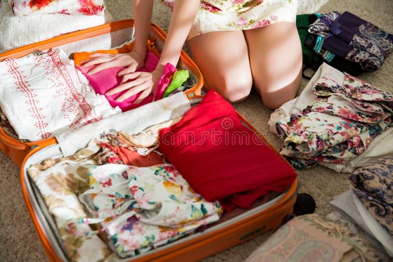 La mujer feliz está embalando cuidadosamente la ropa en la maleta imagenes de archivo