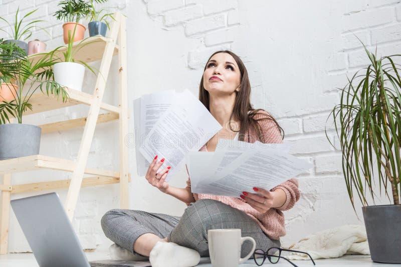 La mujer feliz examina el papel que se sienta cerca del ordenador port?til, la muchacha que el freelancer trabaja con los documen imagen de archivo