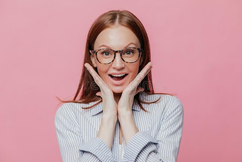 La mujer feliz guarda las manos debajo de la barbilla, siente encantada y satisfecha, lleva los vidrios ópticos y la camisa forma imagenes de archivo