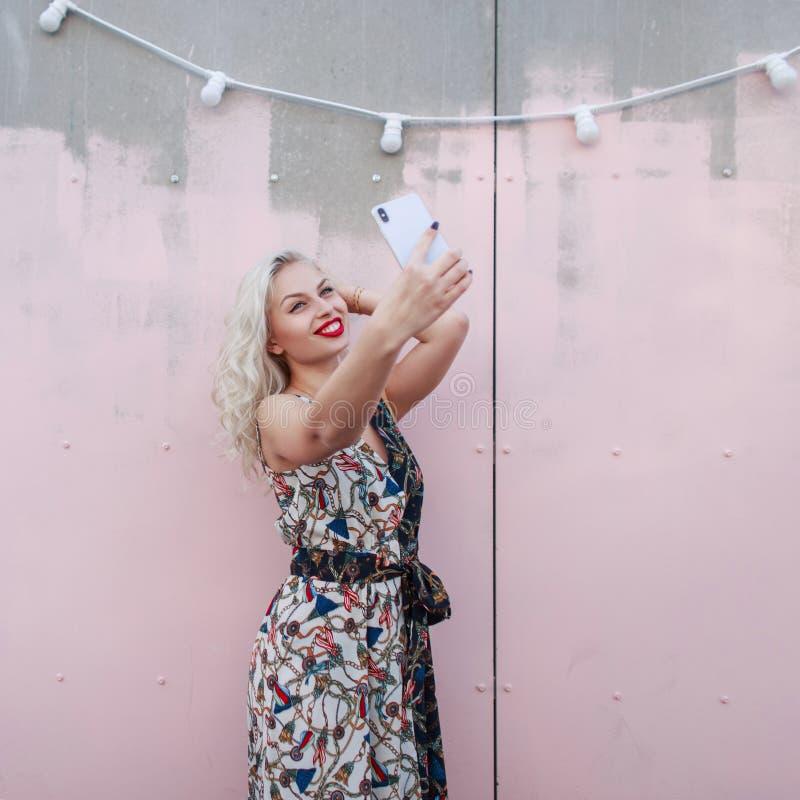 La mujer feliz hermosa joven en un vestido elegante hace el selfie imagen de archivo libre de regalías