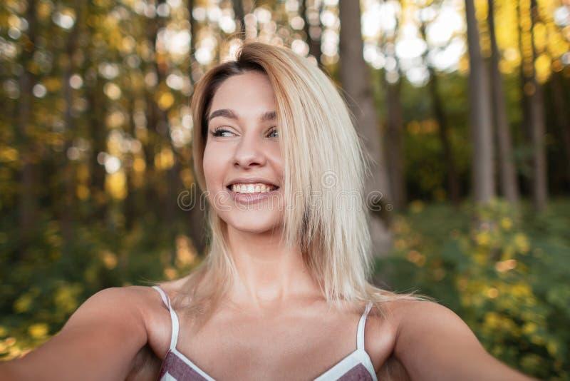 La mujer feliz hermosa joven en un vestido rosado elegante hace el selfie en un smartphone en el bosque entre los árboles foto de archivo